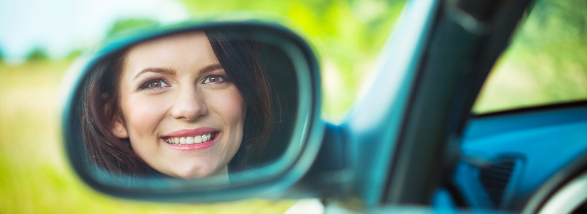 Woman looking in drivers side mirror